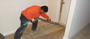 Water Damage Technician Cleaning Up Flooded Carpet